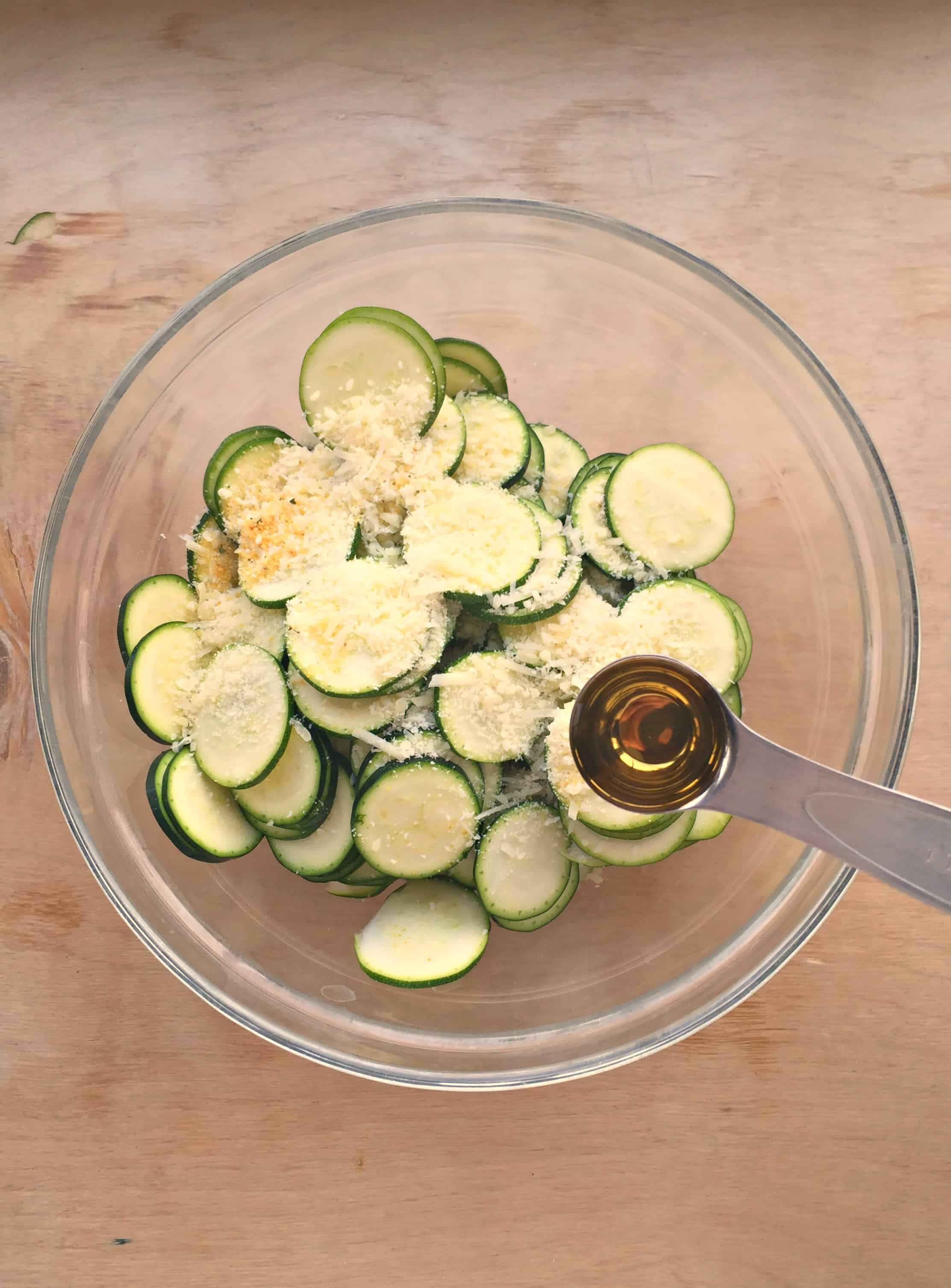 zucchini chips in a bowl with seasoning