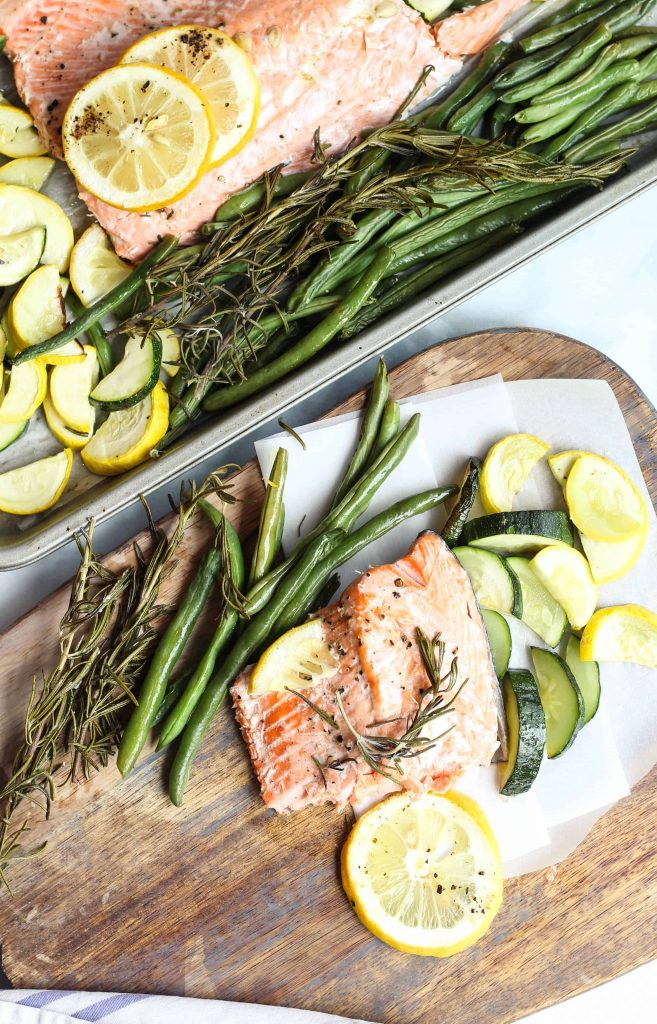 sheet pan salmon with zucchini and lemon on a wooden serving block