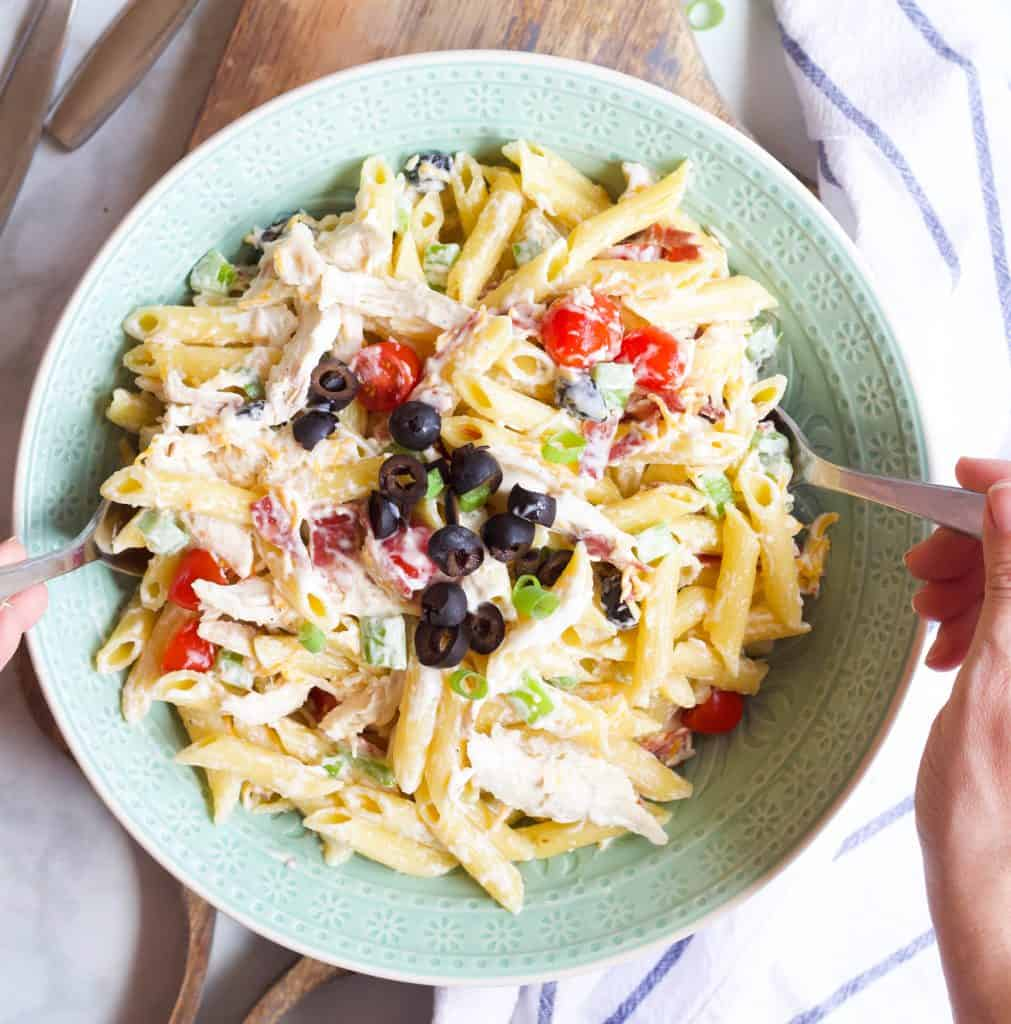 tossing a Chicken Bacon Ranch Pasta Salad