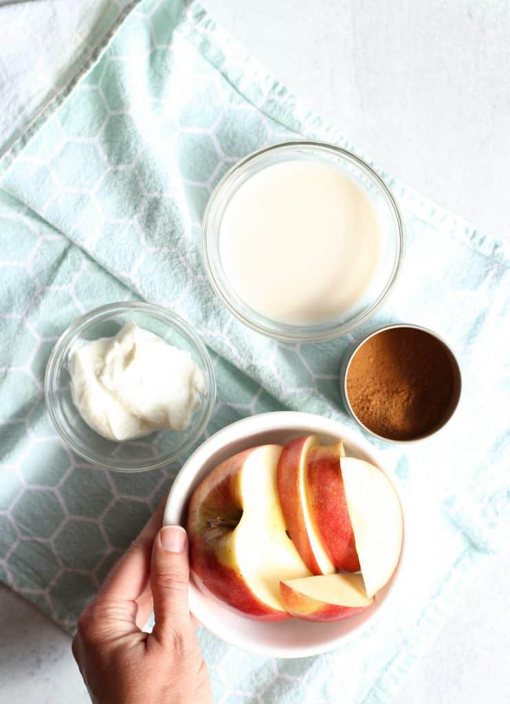 bowl of cut up apples, bowl of greek yogurt, and bowl of almond milk