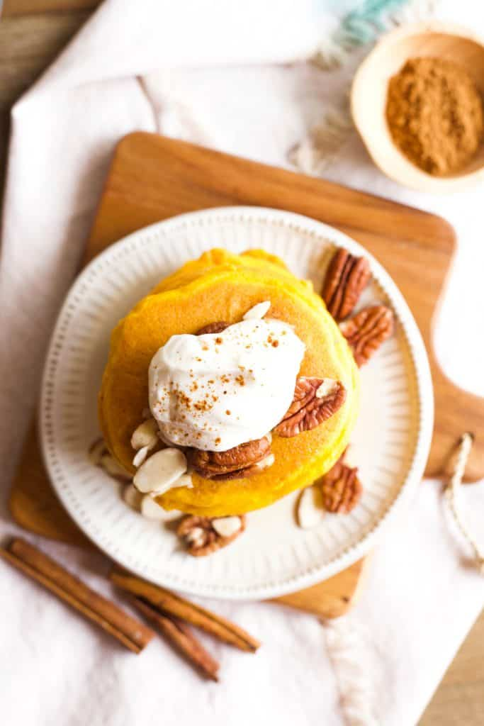 pumpkin pancakes with whipped topping and pecans