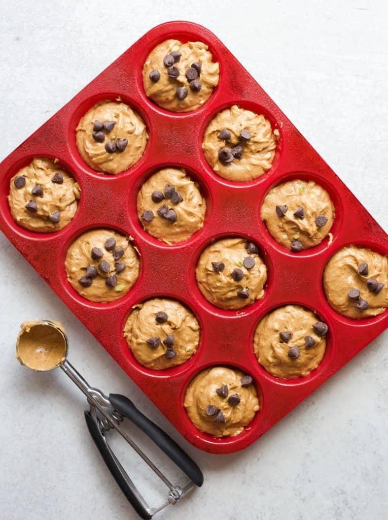 pumpkin zucchini muffin batter in a muffin pan